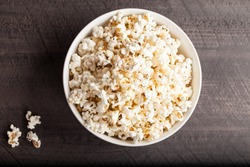 Olive oil popped popcorn in a porcelain bowl top view on a dark wooden background