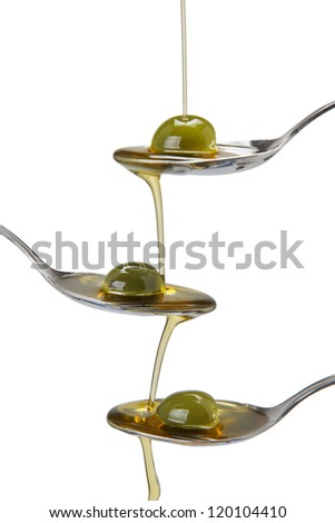 Olive oil poured into a spoon and falling from one to another spoon