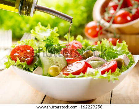 olive oil pouring into bowl of salad