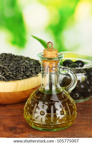 Olive oil small decanter on green background close-up