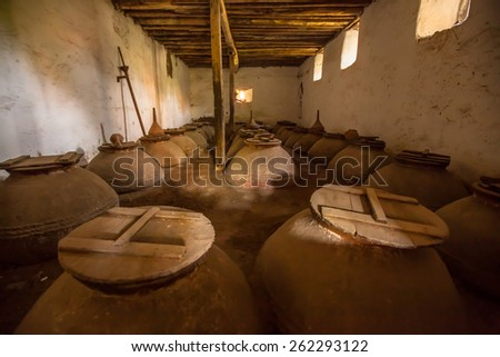 Olive oil storage cellar with Dark brown old historic ceramic pots in Greece