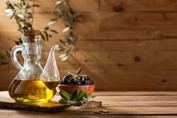 Olive oil with black olives on wooden background