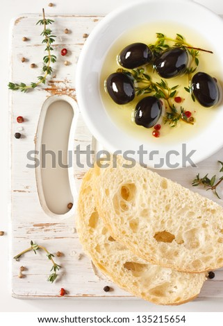 Olive oil with olives and spices. Delicious dip and fresh bread ciabatta.