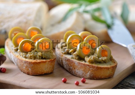 Olive paste on baked olive baguette, decorated with stuffed green olives (stuffed with red bell peppers)
