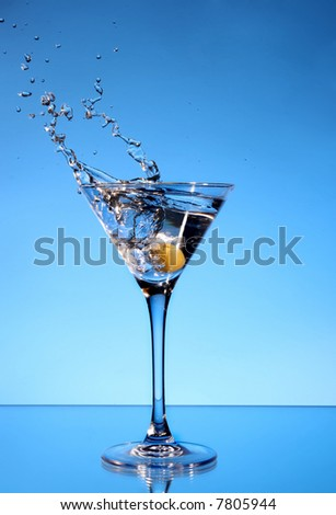Olive splashing in a Martini glass
