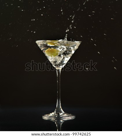 Olive splashing into martini cocktail