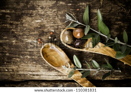 Olive wood spoons with fresh olives and leaves on an old grungy textured wooden tabletop with copyspace