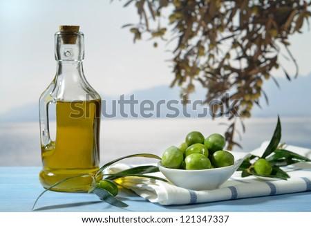 Olives and olive oil against Mediterranean landscape