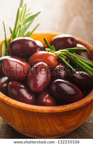 Olives calamata in wooden bowl on the table