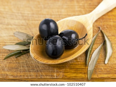 olives on rustic wooden , on  spoon, background