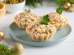 Olivier salad tartlets. Traditional russian appetizer for celebrating new year and christmas. White wooden table background. Fir tree branches, golden balls. Copy space. Close up food.
