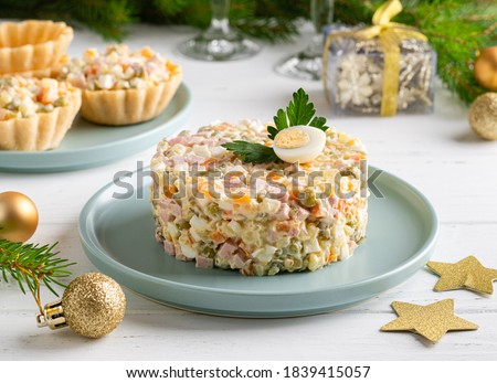 Olivier salad. Traditional russian appetizer for celebrating new year eve and christmas. White wooden table background. Festive table setting. Fir tree branches, golden stars and balls. Close up view.