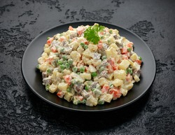 Olivier salad, traditional Russian food in black plate on black rustic table