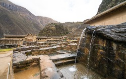 Ollantaytambo - A fountain, part of the Inca domestic water supply, Inca ruins in the background. Sacred Valley, Peru.