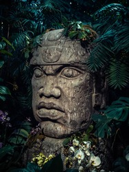 Olmec sculpture carved from stone. Mayan symbol - Big stone head statue in a jungle