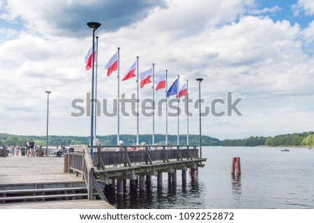 Olsztyn, Poland - May 1, 2018: Polish and EU flags on pier on Ukiel lake. #1092252872