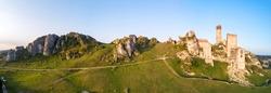 Olsztyn, Silesia, Poland. Wide panorama of ruins of medieval royal castle on the limestone rocks in Polish Jurassic Highland near Czestochowa. Aerial view in sunrise light in summer.
