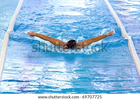 Olympic swimmer during butterfly stroke training in indoor swimming pool.