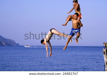 OLYMPOS, TURKEY -  AUGUST 3: Foreign and local tourist jump into sea from pier on August 3, 2007 in Olympos, Turkey. Olympos is located 90 km southwest of Antalya city near Kemer.