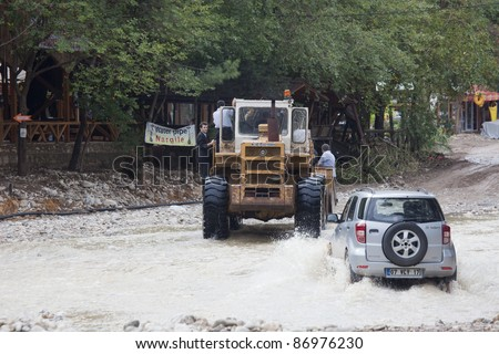 OLYMPOS, TURKEY - OCTOBER 14: Bulldozer and Off-Road Vehicle cross flooded road after flood disaster on October 14, 2009 in Olympos, Turkey. The floods destroy roads and houses.