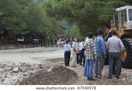 OLYMPOS, TURKEY - OCTOBER 14:  Politicians and civil servants waiting for earth mover used  as a ferry for crossing overflooded road after flood disaster on October 14, 2009 in Olympos, Turkey.