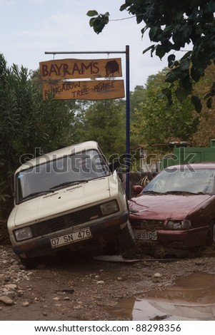 OLYMPOS, TURKEY - OCTOBER 14: Two crashed cars in front of tree houses after flood disaster on October 14, 2009 in Olympos, Turkey, Asia. The floods destroy roads and swept away about 50 cars.