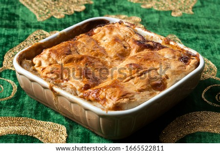 Om Ali, Umm Ali or Oum Ali is a traditional and popular Egyptian dessert. Egyptian Bread Pudding. Arabic cuisine, Egypt culture concepts. Horizontal close-up on vintage green background. Stock photo ©
