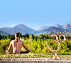 Om statue and man doing meditation at mountain background. Free space for text