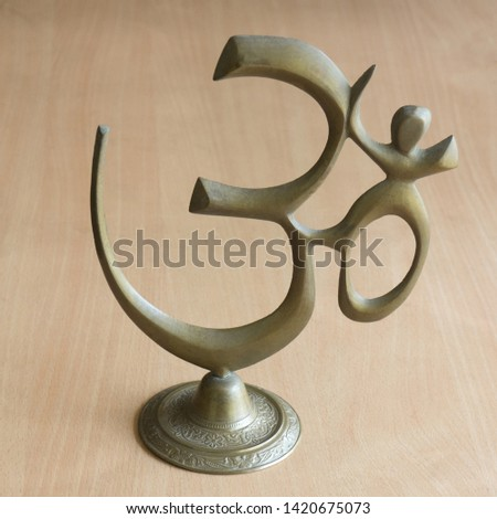 Om symbol from yellow metal on a wood background #1420675073