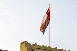Oman flag standing on top of a building with golden light hitting the flag
