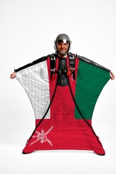 Oman flag travel. Bird Men in wing suit flag. Sky diving men in parashute. Patriotism, men and flag.