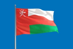 Oman national flag waving in the wind on a deep blue sky. High quality fabric. International relations concept.
