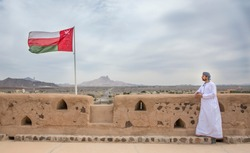 omani man in traditional outfit ilooking at the landscape of remote countryside