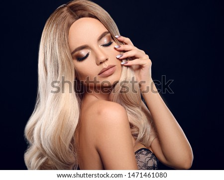 Ombre blond curly hair. Beauty fashion blonde woman portrait. Beautiful girl model with makeup, long healthy hairstyle posing isolated on studio black background.