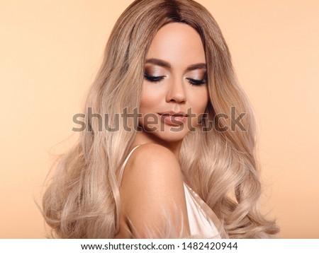 Ombre blond hairstyle. Beauty fashion blonde portrait. Sexy woman wears in pink fur coat. Beautiful girl model with makeup, long healthy hair style posing isolated on studio beige background.