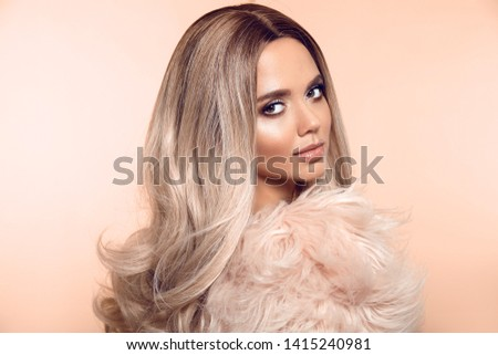 Ombre blond hairstyle. Beauty fashion blonde portrait. Sexy woman wears pink fur coat. Beautiful girl model with makeup, long healthy hair style posing isolated on studio beige background.