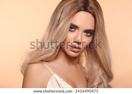 Ombre blond hairstyle. Beauty fashion blonde woman portrait. Beautiful girl model with makeup, long healthy hair style posing isolated on studio beige background.