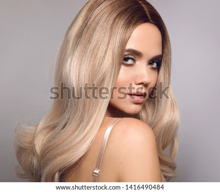Ombre blond shiny hair. Beauty fashion blonde woman portrait. Beautiful girl model with makeup, long healthy hairstyle posing isolated on studio grey background.