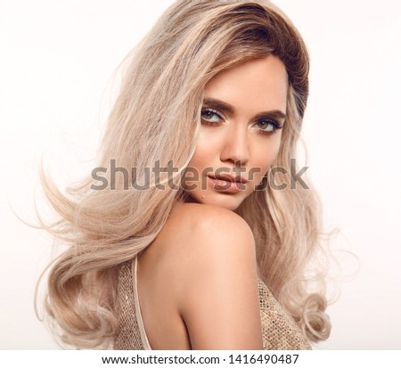 Ombre blond wavy hair. Beauty fashion blonde woman portrait. Beautiful girl model with makeup, long healthy hairstyle posing isolated on studio white background.
