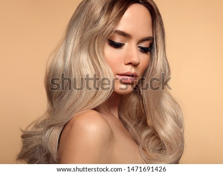 Ombre blond wavy hairstyle. Beauty fashion blonde woman portrait. Beautiful girl model with makeup, long healthy hair style posing isolated on studio beige background. #1471691426
