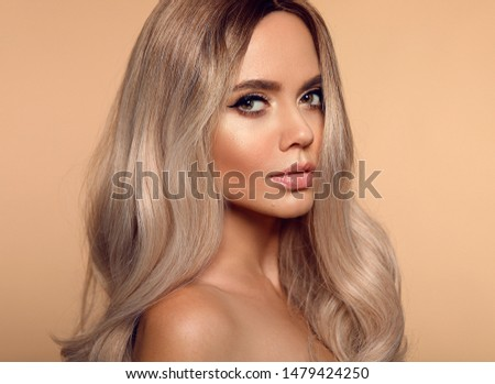 Ombre blond wavy hairstyle. Beauty fashion blonde woman portrait. Beautiful girl model with makeup, long healthy hair style posing isolated on studio beige background. #1479424250