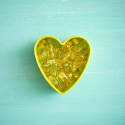 Omega-3 capsules are poured into a heart shape on a turquoise background. Close-up. Health concept with fish oil capsules.
