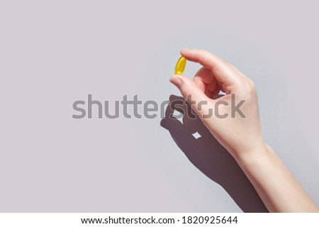 Omega 3 gel capsule. Yellow vitamin. Health eating. Dietology. Fish oil supplement. Microdosing concept. Golden color softgel collagen. Hand holding drug. Two bowl. Medicine immunity cosmetics Stockfoto ©