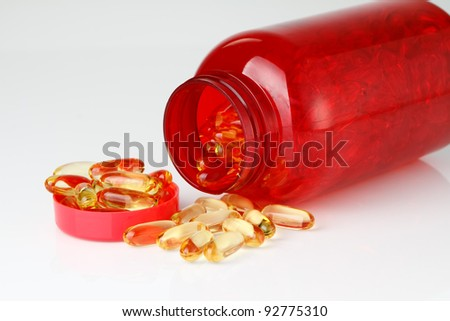 Omega 3 oil fish capsules with red plastic bottle on white background focused to the bottle