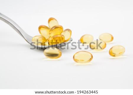 Omega-3 pills on spoon.