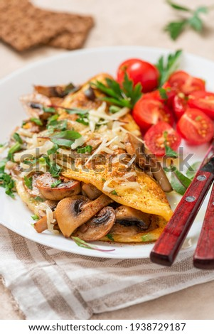 Omelet with mushrooms close-up. Tasty breakfast or lunch. Omelet with champignons, cheese, and tomatoes in a white plate on the table.  Stockfoto ©