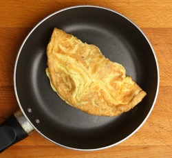 Omelette cooking in frying pan.
