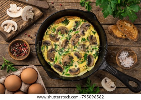 omelette with mushrooms on cast iron pan, top view, wooden background #795096562
