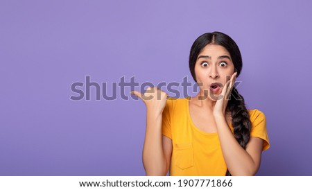 Omg, Cool Offer. Surprised young indian lady pointing at free space isolated over purple studio background. Excited shocked woman showing copy space and place for advert or promotional text, banner