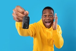 Omg, New Car. Emotional African American Man Showing Automobile Key And Shouting In Shock And Excitement Posing On Blue Background, Looking At Camera. Studio Shot. Own Auto Concept
